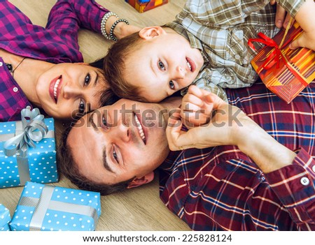 Happy smiling young family with gifts lying on the floor - stock photo