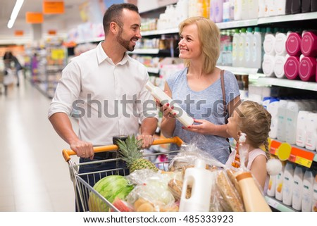 Happy smiling young family with trolley selecting shampoo  in supermarket