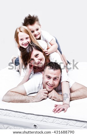 happy smiling young family with two children lying on mattress
