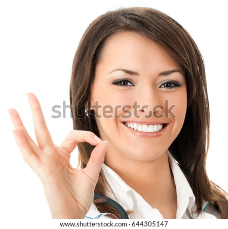 Happy smiling young female doctor with okay gesture, isolated over white background. Medicare, health care and medical occupation concept shot.