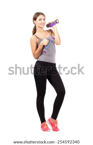Happy smiling young female posing while holding dumb bells looking at camera. Full body length portrait isolated over white background. - stock photo