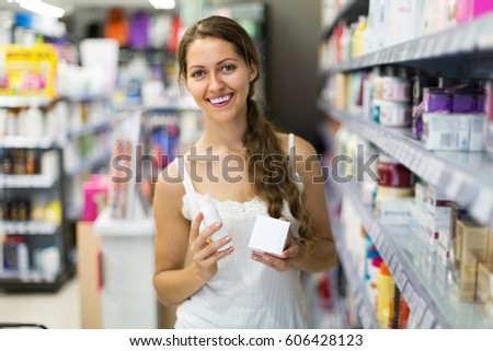 Happy smiling young girl choosing cream for herself in the shop