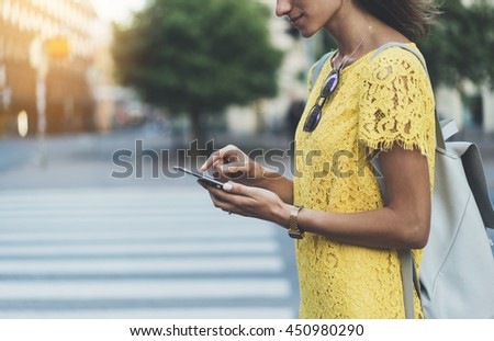 Happy smiling young girl using modern smart phone while standing at crosswalk, hipster girl writing text message on internet via cellphone, attractive woman wearing yellow dress, walking in the city  - stock photo