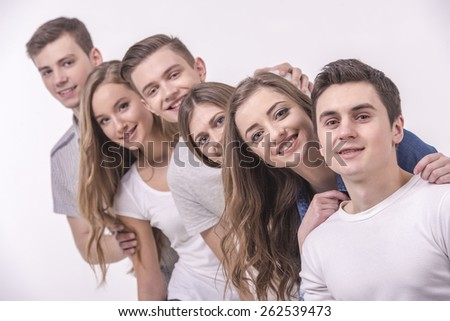 Happy smiling young group looking at camera. isolated on grey background.