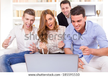 Happy smiling young group of friends watching and working together at laptop, cheering