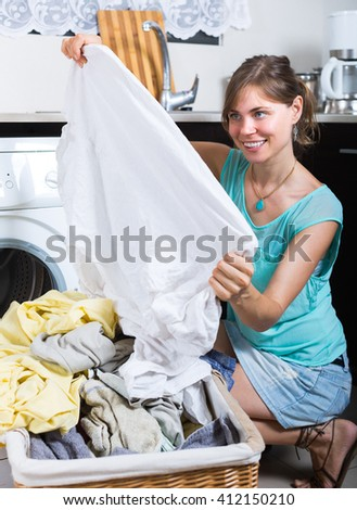 Happy smiling young housewife with basket of linen near washing machine - stock photo