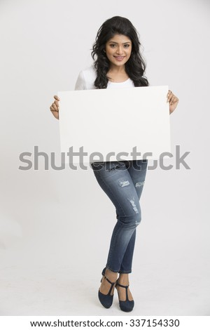 Happy smiling young Indian woman holding a blank billboard white background - stock photo