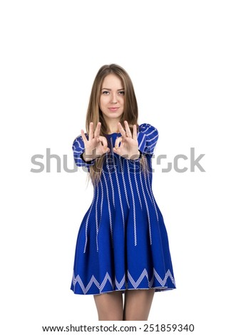 Happy smiling young lady with OK hand sign. Portrait of young Caucasian lady makes OK hand sign with both hands stretched forward. Bright casual dress and white background - stock photo