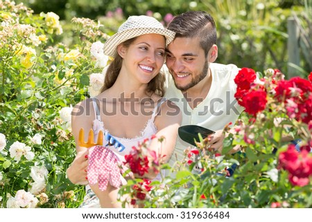 Happy smiling young man and woman caring their garden together