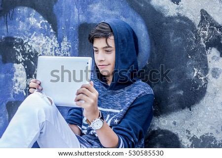 Happy smiling teenager looking his pad stock photo 530582347 happy smiling young man boy holding looking at tablet pad computer present touch screen voltagebd Images