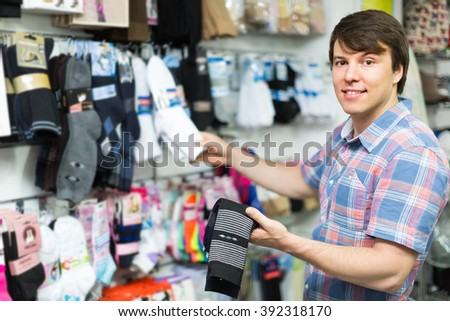Happy smiling young man buying socks at store  - stock photo