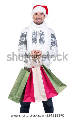 Happy smiling young man in Santa Claus hat with shopping bags, isolated on white background - stock photo
