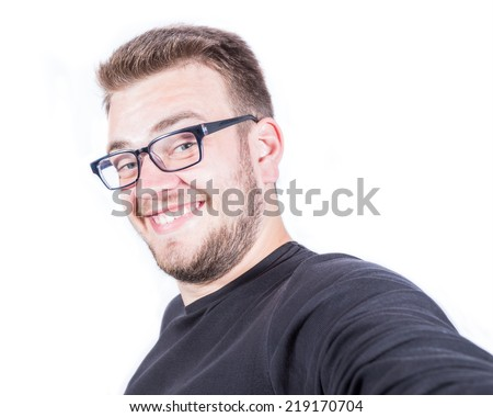 Happy smiling young man taking a selfie photo. Isolated on white background - stock photo