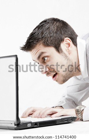 Happy smiling young man watching and working on computer laptop, isolated on white.