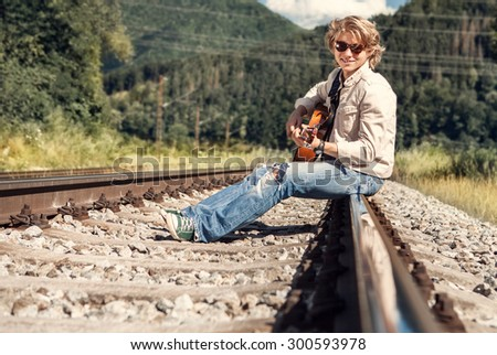 Happy smiling young man with guitar sitting on railway - stock photo