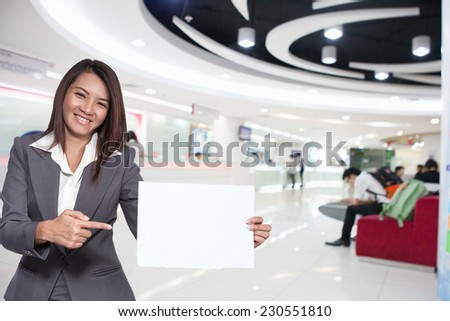 Happy smiling young pretty attractive brunette Asian business woman standing positive showing blank signboard, on counter services background - stock photo