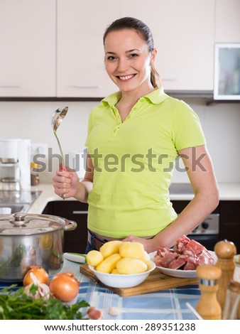 Happy smiling young woman cooking with meat and potatoes at kitchen