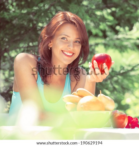 Happy Smiling Young Woman Eating Organic Apple at her Garden. Vintage style photo