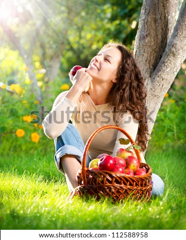 Happy Smiling Young Woman Eating Organic Apple in the Orchard.Basket of Apples. Harvest Concept.Garden - stock photo