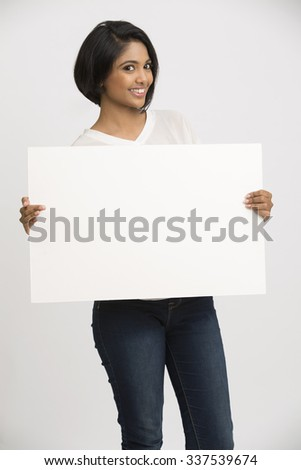 Happy smiling young woman holding a blank billboard white background - stock photo