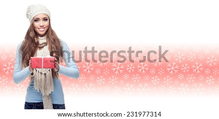 happy smiling young woman holding gift over winter snowflakes background