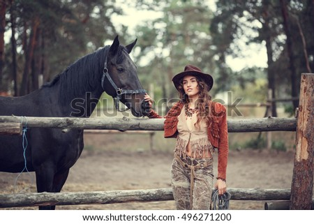 Happy smiling young woman in cowboy hat with a horse at the farm