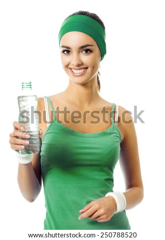 Happy smiling young woman in green fitness wear drinking water, isolated against white background - stock photo