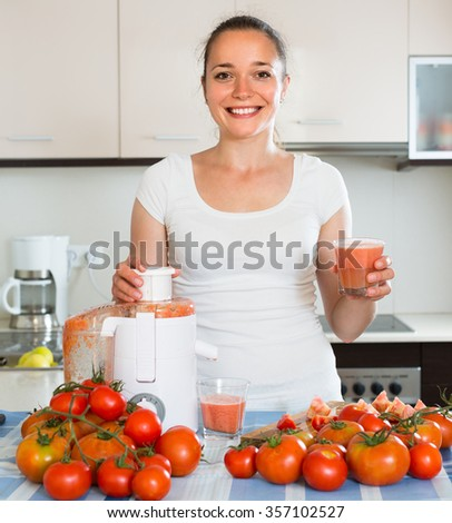 Happy smiling young woman making juice from tomatoes at home kitchen