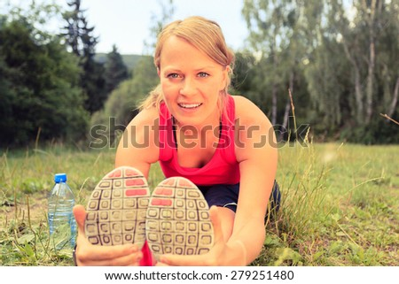 Happy Smiling Young Woman Runner Exercising and Stretching Fitness in Summer Nature Outdoors, Healthy Lifestyle Activity Motivation and Inspiration Outside. Training and Working Out Healthy Lifestyle - stock photo