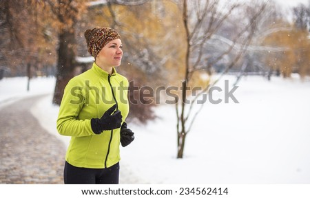 Happy smiling young woman running in snowing winter  - stock photo