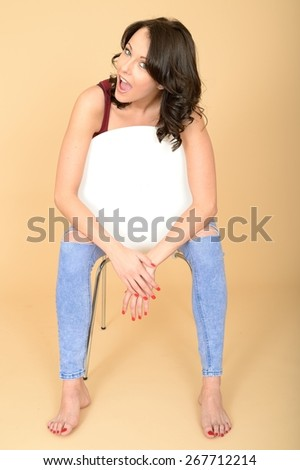 Happy Smiling Young Woman Sitting in a White Chair Relaxing in Bare Feet - stock photo