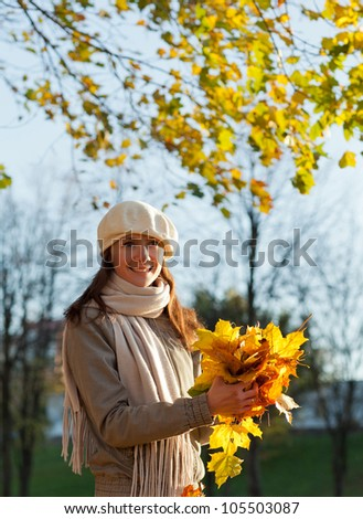Happy smiling young woman throwing leaves in autumn park