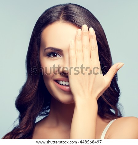 Happy smiling young woman with one eye, closed by hand, covering part of her face