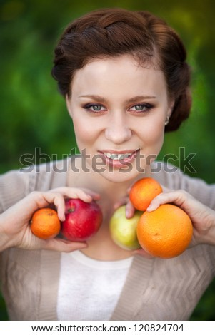 Happy Smiling Young Woman with Organic apple and orange in orchard. Harvest Concept. Brunette cute girl with fresh fruits in green garden grass. Provence lady with hairstyle outdoor with healthy food