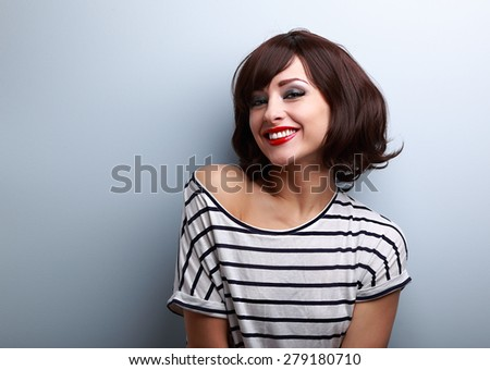 Happy smiling young woman with short hair on blue copy space background - stock photo