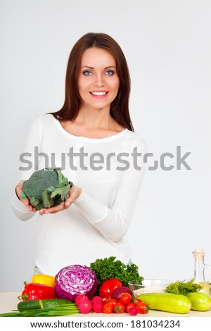 happy smiling young woman with vegetables over white wall - stock photo