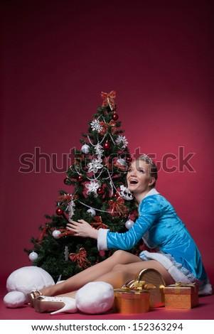Happy Snow Maiden posing with Christmas tree - stock photo