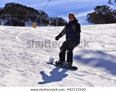 Happy snowboarder slides down the track in Snowy Mountains ski resort of Perisher Valley, kosciuszko national park. - stock photo