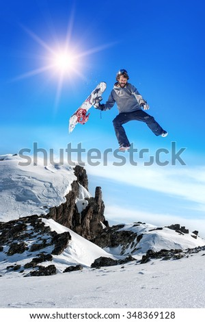 Happy Snowboarder. Snowboarder man holding snowboard in the air jumping with mountains on background