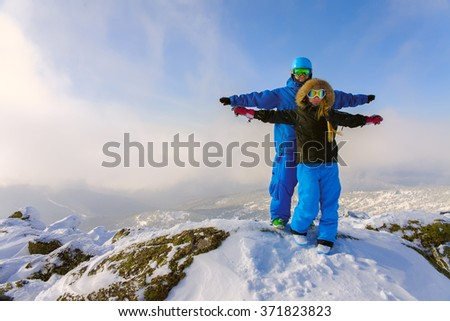 Happy snowboarding couple in winter mountains