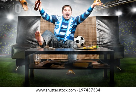 happy soccer or football fan on sofa at stadium - stock photo