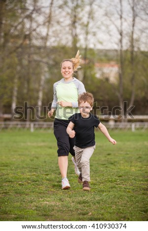 Happy son and mother doing exercises in the summer park. on the stadium, outdoor. Sport activities with children. Healthy lifestyle. Fitness exercises. Young mother and son running together - stock photo