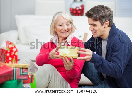 Happy son giving Christmas gift to mother at home