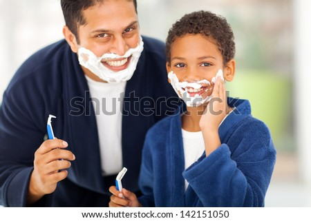 happy son playing with father's shaving foam at home - stock photo