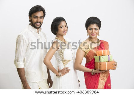 Happy South Indian traditional family holding gift boxes on white background. - stock photo