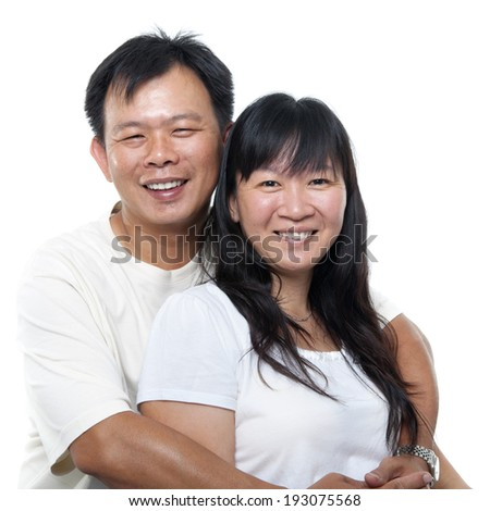 Happy southeast Asian mature couple hugging and smiling, isolated on white background. - stock photo