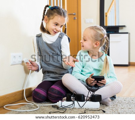 happy spanish children playing with sockets and electricity indoors