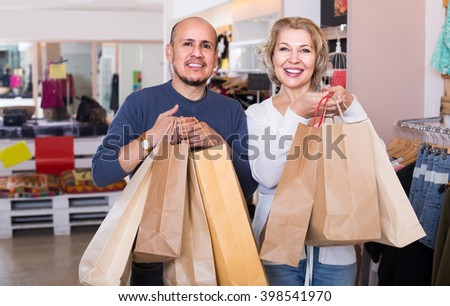Happy spanish senior couple with purchases in bags at apparel store