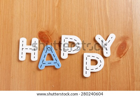 HAPPY, spell by woody puzzle letters with woody background - stock photo