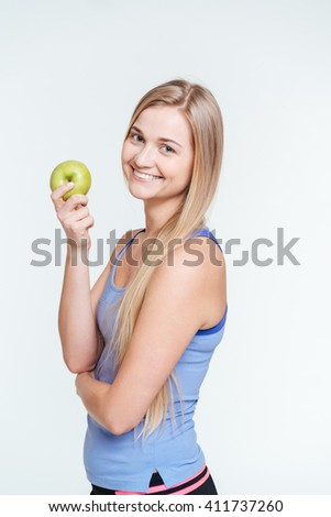 Happy sports woman holding apple isolated on a white background - stock photo